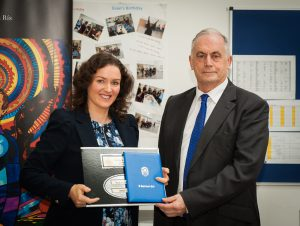 Ms Maria Gibney Rodgers, daughter of Mr James Gibney, First teacher, receives a presentation from Mr David Neville